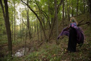 women in forest twirling with shawl