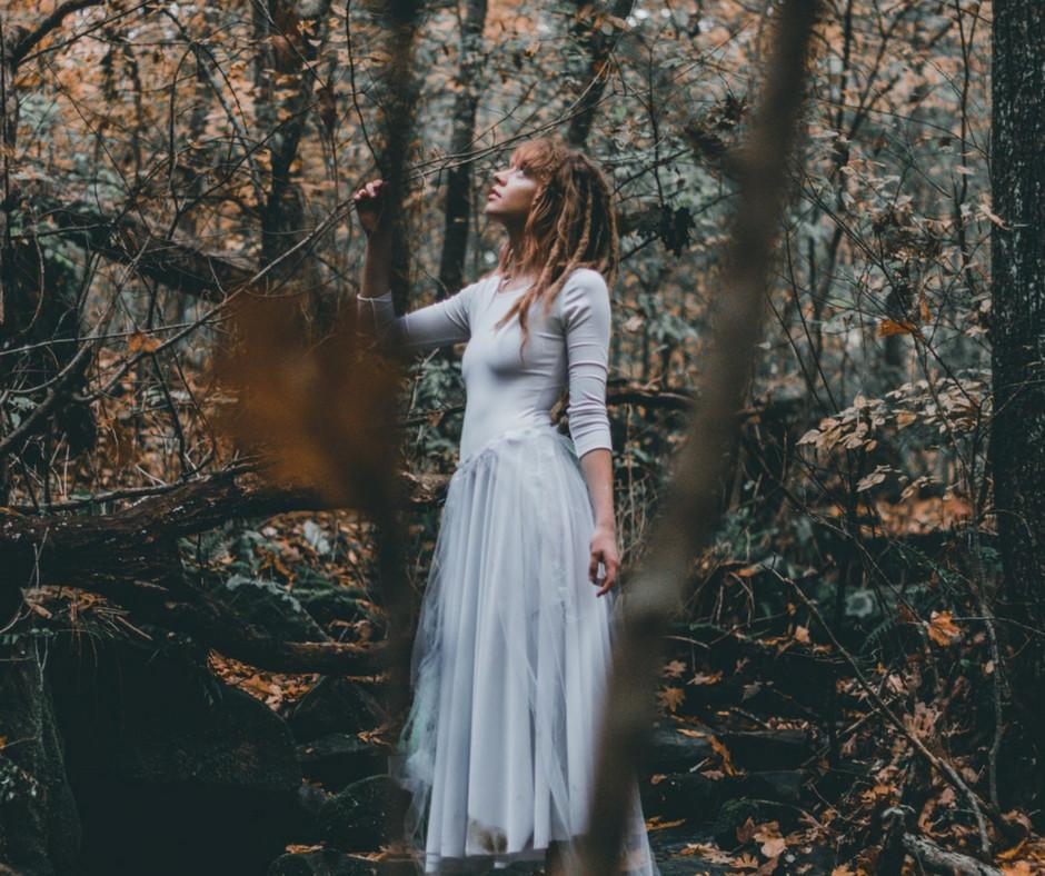 girl in white dress in the woods barefoot