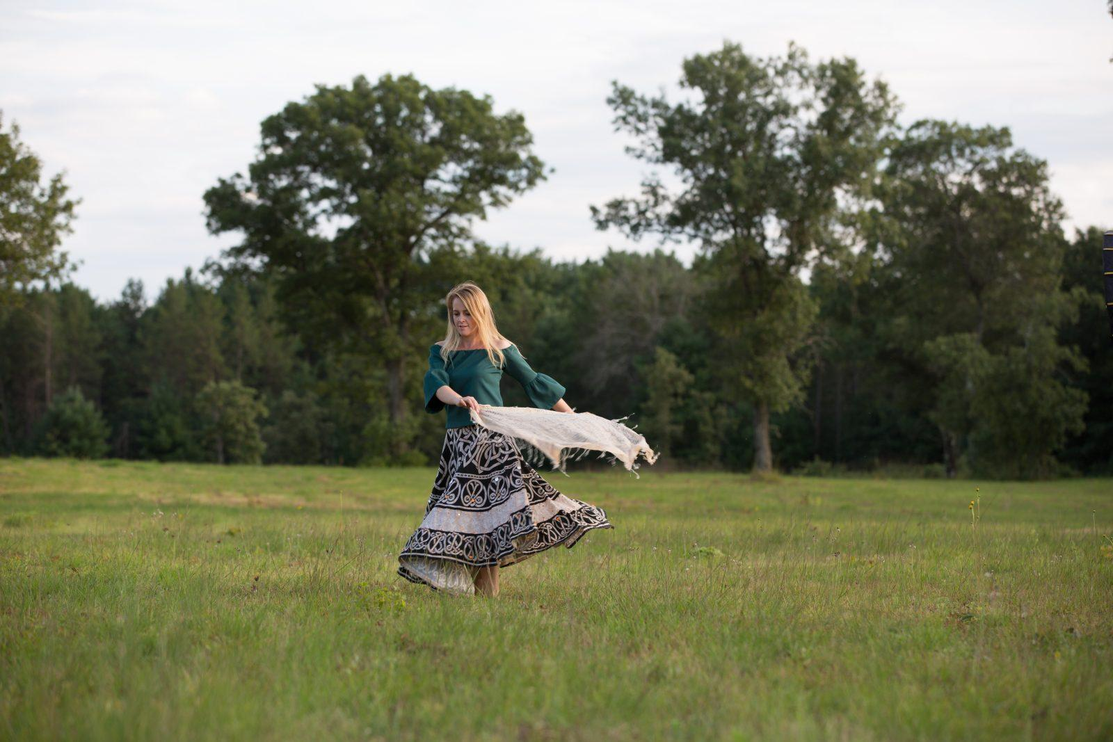 lady in field with shawl spinning